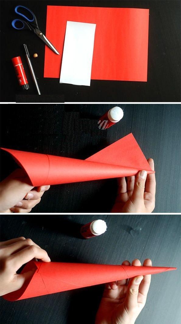 Dùng giấy màu đỏ cuốn thành hình chóp, rồi dùng keo dán cố định lại.